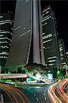 Lumière de voiture sentiers sous les gratte-ciel et bâtiments de la ville