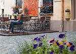 Woman sitting at cafe in Jana Seta, Riga, Latvi.
