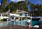 Woman sitting by pool in Bhu Nga Thani Resort and Spa, Railay, Krabi Province, Thailan.