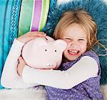 Fille souriante pose dans son lit avec piggy bank