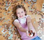 Fille pose sur plancher avec poignée de pièces de monnaie