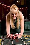 Woman gathering winnings at craps table