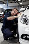 Mechanic waxing new car in showroom