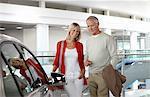 Couple regardant une voiture neuve en show-room