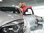 Couple à la nouvelle voiture dans la salle d'exposition