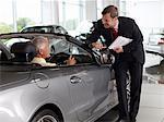 Salesman talking to man in convertible in automobile showroom