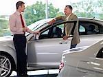 Salesman talking to man in automobile showroom