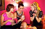 Three beautiful women giving gifts in a bar