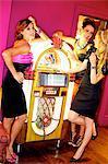 Three beautiful women next to a jukebox