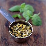 Camomille et thé à la menthe feuilles dans une passoire