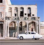 Classic white car passing rundown building