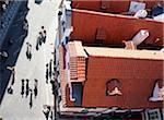 Menschen gehen auf Kopfsteinpflaster neben Gebäuden, Luftbild