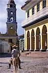 Man riding horse near colonial buildings