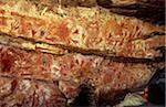 Australie, Northern Territory, terre d'Arnhem, nr Mt Borradaile. Un visiteur se penche en arrière pour voir art rupestre aborigène dans un abri « Major Art »