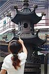 Femme injecter de l'argent dans l'urne pour chance, Temple Liurong, Guangzhou, Guangdong Province, Chine