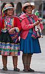 Peru, Two Indigenous Peruvian woman wearing traditional costume in Cusco s main square, Plaza de Armas.