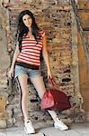 Woman holding bag at brick wall