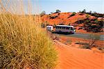 Australia, Northern Territory, Lasseter Highway.  A bus drives through the arid desert scenery of central Australia.