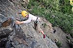Woman rock climbing along Turnagain Arm near Anchorage, Southcentral Alaska, Summer