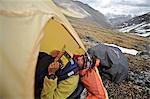 Backpacker reads a book inside a tent and waits out inclement weather at an alpine camp below Mt. Chamberln, Brooks Range, ANWR, Arctic Alaska, Summer