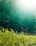 A boy fishing by a calm lake.
