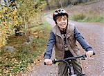 A boy bicykling on a gravelroad.