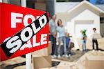 Schild am Haus mit Familie im Hintergrund verkauft