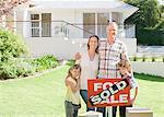 Familie stehend mit verkauften Zeichen für ihr neues Haus