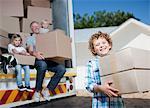Famille transportant des boîtes de camion de déménagement