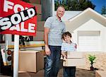 Père et fils avec boîtes debout près signe vendus pour leur nouvelle maison