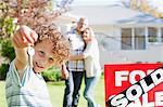 Boy holding neue Haus Schlüssel neben verkauft Zeichen