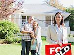 Grundstücksmakler stehend mit Familie vor neuen Haus