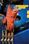 Gants de travail colorent au bitume suspendus sur machine en fabrique de dalles de moquette