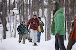 Junge Menschen laufen mit Schneeschuhen