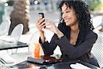 Femme d'affaires avec téléphone cellulaire au Cafe