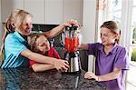 Girls mixing fruit in blender