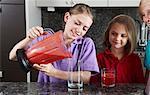 Girls pouring fruit juice from blender