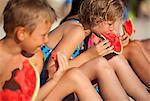 Enfants mangeant melon d'eau sur la plage