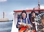 Fishermen on fishing boat with fish