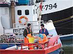 Fishermen on fishing boat in harbour