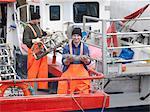 Pêcheur détient des poissons sur le bateau dans le port
