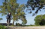 Man with mountain bike under blue skies