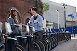 Jeune couple parlant avec vélos loués