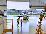 Engineers in jet aircraft hangar