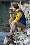 Man on lake drinking hot beverage