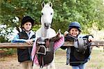 Girls with pony holding saddles