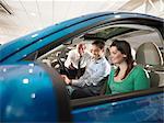 Salesman shows customers a car