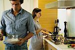 Couple dans la cuisine, la femme tandis que l'homme définit la table de cuisson