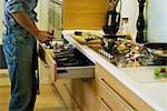 Homme, cuisiner, prendre ustensile hors de tiroir