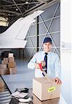 Worker taping box in hangar